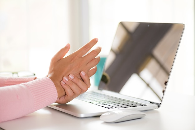 Donna del primo piano che tiene il suo dolore del polso dall'utilizzo del computer. sindrome da ufficio.