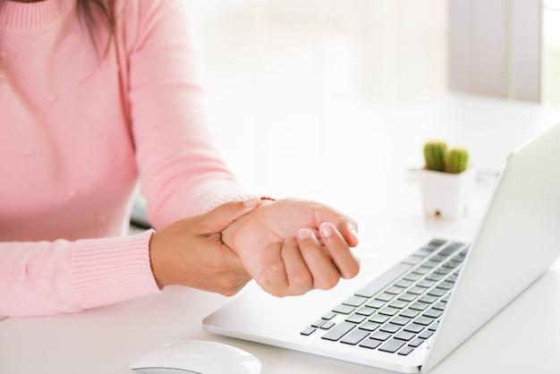 Donna del primo piano che tiene il suo dolore del polso dall'utilizzo del computer. sindrome da ufficio