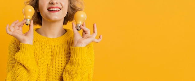 Donna del primo piano che tiene le lampadine gialle