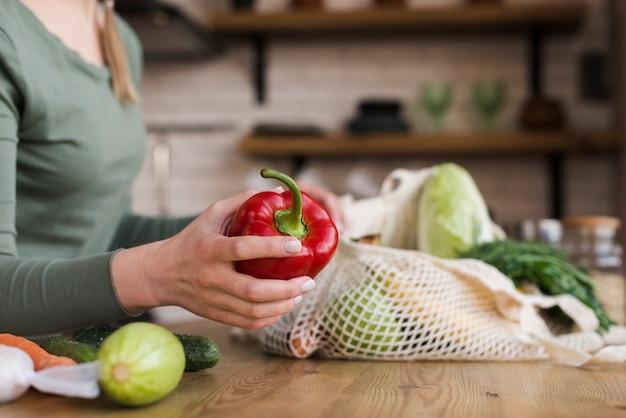 Donna del primo piano che tiene le verdure organiche