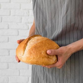 Donna del primo piano che tiene pane fresco