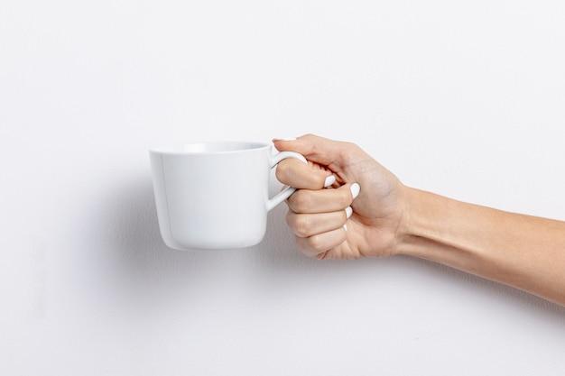 Donna del primo piano che tiene tazza vuota bianca