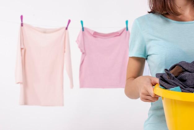 Donna del primo piano che tiene un cestino di lavanderia giallo
