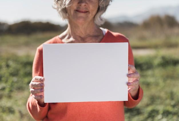 Donna del primo piano che tiene un pezzo di carta