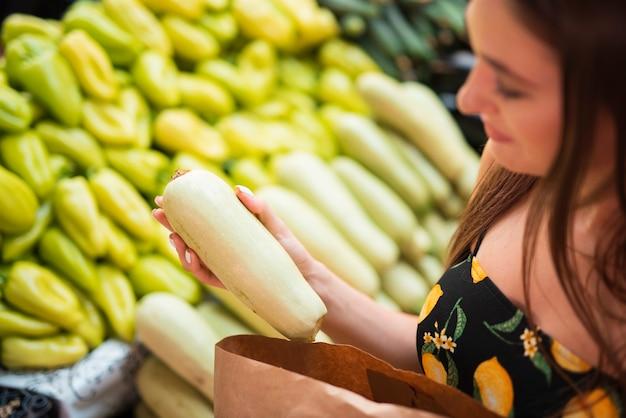 Donna del primo piano che tiene uno zucchini bianco