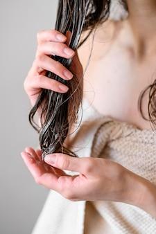Donna del primo piano che usando balsamo per capelli