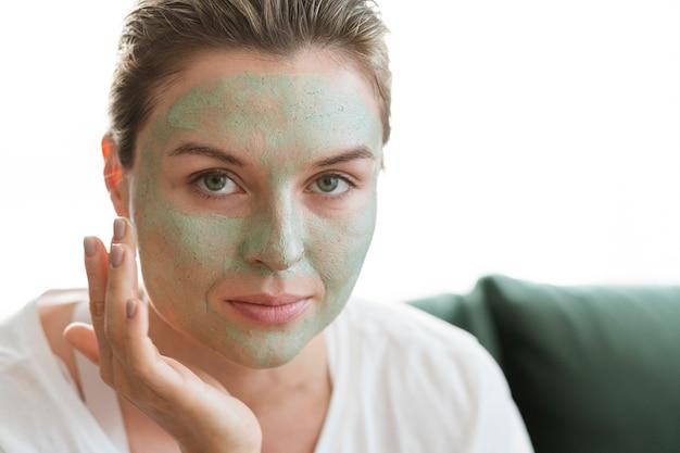 Donna del primo piano che usando la maschera facciale sana naturale