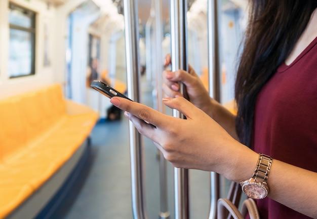 Donna del primo piano che utilizza il telefono cellulare astuto nel bts skytrain