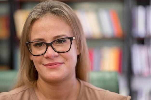Donna del primo piano con gli occhiali in biblioteca