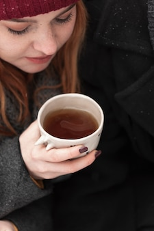Donna del primo piano con i vestiti di inverno che tengono tazza di tè