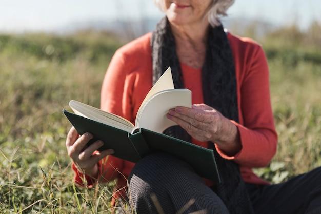 Donna del primo piano con il libro all'aperto