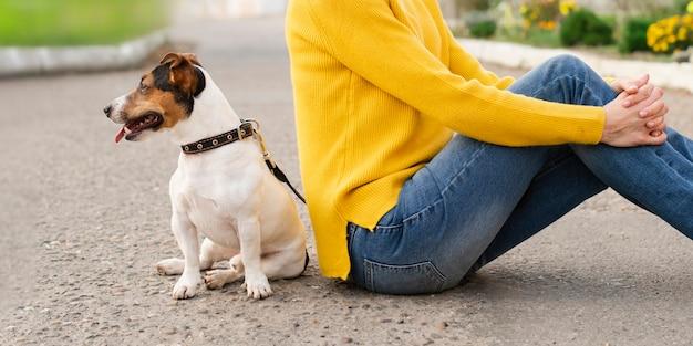 Donna del primo piano con il suo cane all'aperto