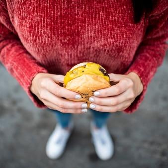 Donna del primo piano con l'angolo alto del cheeseburger