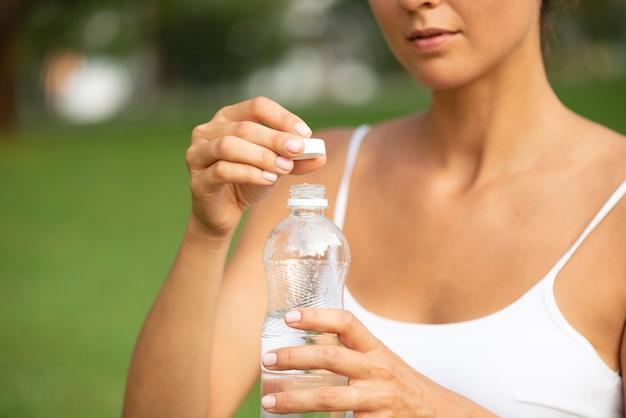 Donna del primo piano con la bottiglia di acqua