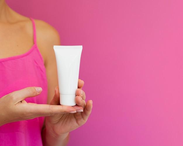 Donna del primo piano con la camicia rosa e la bottiglia crema