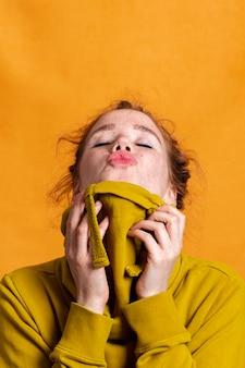 Donna del primo piano con la maglia con cappuccio gialla e il fondo arancio