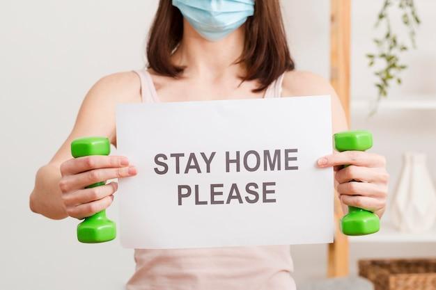 Donna del primo piano con la maschera e messaggio di soggiorno a casa