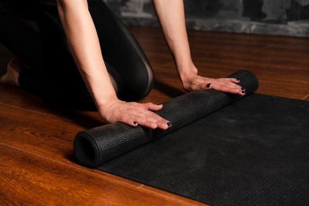 Donna del primo piano con la stuoia di yoga