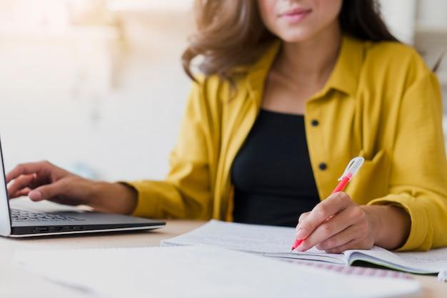 Donna del primo piano con scrittura del computer portatile