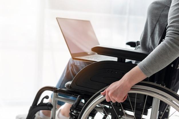 Donna del primo piano in sedia a rotelle che lavora ad un computer portatile