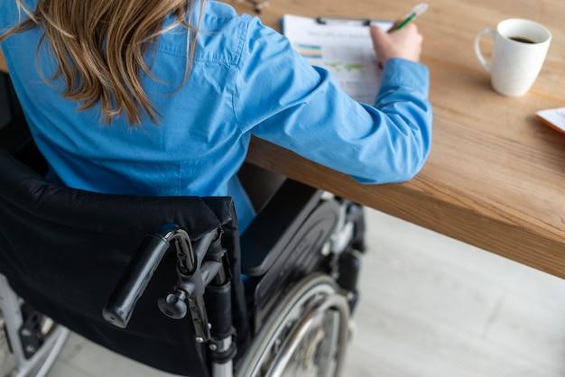 Donna del primo piano in sedia a rotelle che lavora all'ufficio