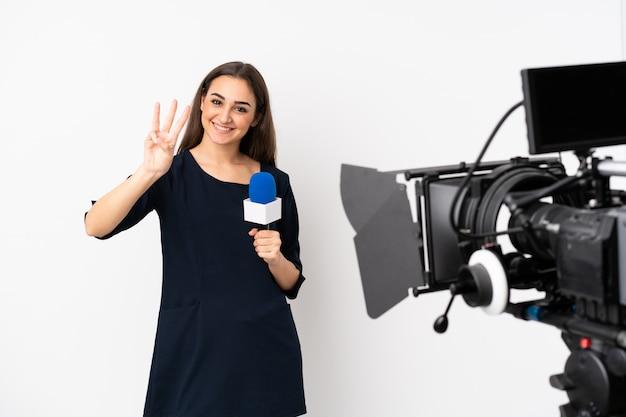 Donna del reporter che tiene un microfono e che riferisce le notizie isolate sulla parete bianca felice e che conta tre con le dita