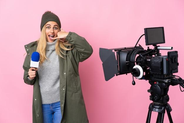Donna del reporter che tiene un microfono e che riferisce le notizie sopra il gesto di fabbricazione rosa isolato del telefono. richiamami segno