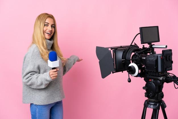 Donna del reporter che tiene un microfono e che riferisce le notizie sopra le mani estendentesi isolate di rosa al lato per l'invito a venire