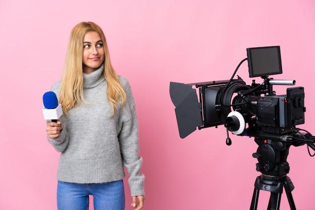 Donna del reporter che tiene un microfono e che riferisce le notizie sopra spazio rosa isolato che fa gesto di dubbi che sembra laterale