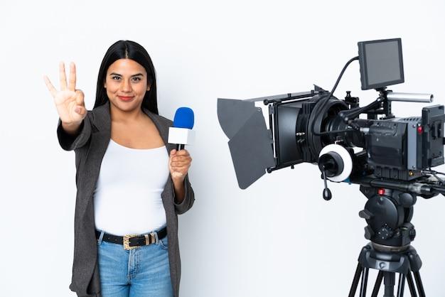 Donna del reporter che tiene un microfono e che riferisce le notizie sulla parete bianca felice e che conta tre con le dita