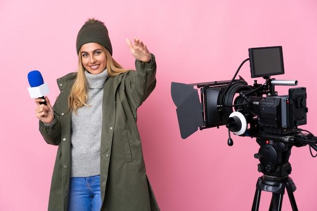 Donna del reporter che tiene un microfono e che riferisce le notizie sulla presentazione rosa isolata e che invita a venire con la mano