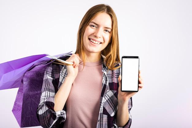Donna del ritratto che mostra telefono alla macchina fotografica