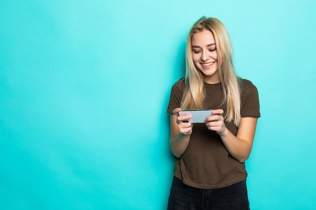 Donna del ritratto divertendosi aggeggio del dispositivo del gioco isolato sopra la parete blu