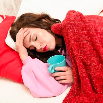 Donna del tiro medio che ha mal di testa mentre resta a letto