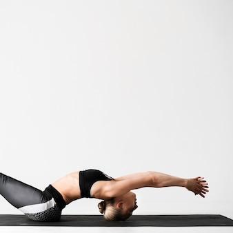 Donna del tiro medio sulla stuoia di yoga