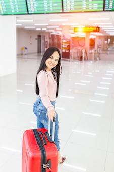 Donna del viaggiatore che cammina portando una valigia in aeroporto internazionale