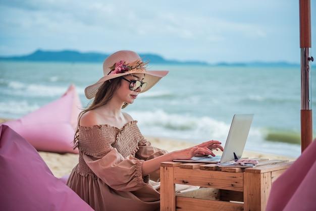 Donna del viaggiatore che lavora al computer portatile sulla spiaggia.