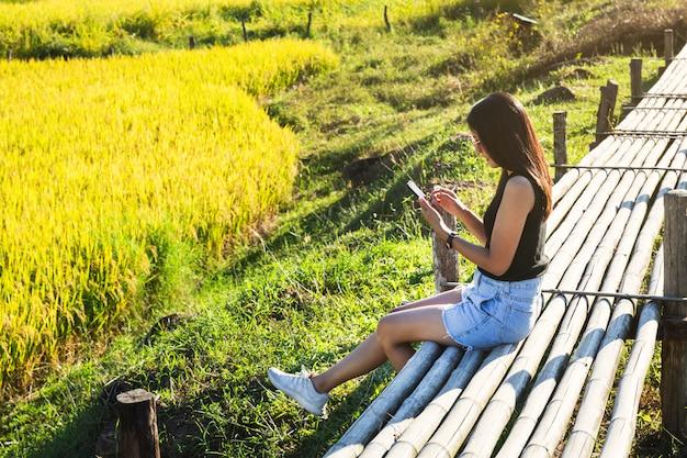 Donna del viaggiatore che per mezzo del telefono cellulare