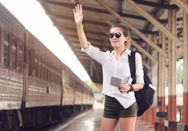 Donna del viaggiatore con gli occhiali che ondeggiano la sua mano felice di incontrare il suo amico alla stazione ferroviaria