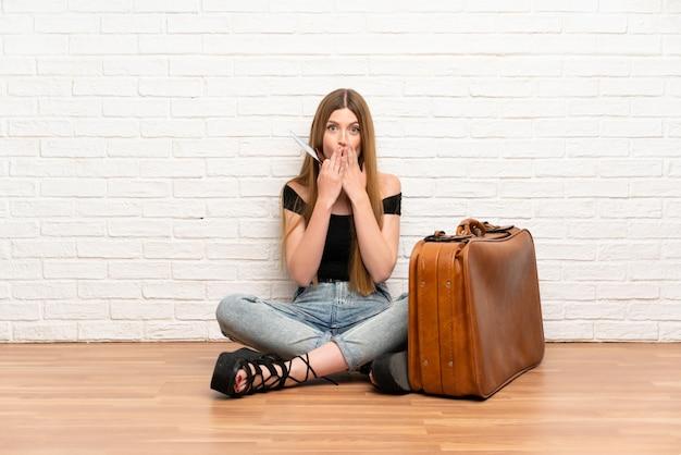 Donna del viaggiatore con la valigia e la carta d'imbarco con espressione facciale di sorpresa