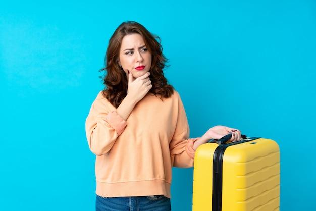 Donna del viaggiatore con la valigia sopra la parete isolata