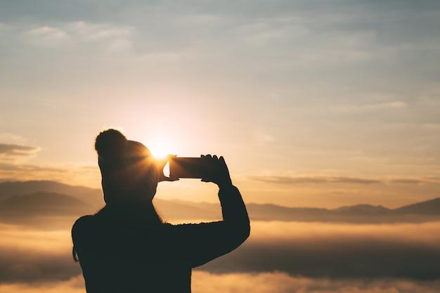 Donna del viaggiatore con lo smartphone che prende foto di bello paesaggio