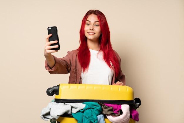 Donna del viaggiatore con una valigia piena di vestiti isolati sulla parete beige che fa un selfie