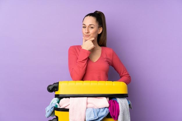 Donna del viaggiatore con una valigia piena di vestiti sopra la risata viola isolata della parete