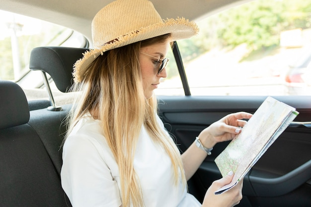 Donna del viaggiatore in un'automobile che esamina mappa