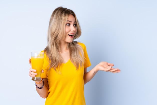 Donna dell'adolescente che giudica un succo d'arancia isolato sulla parete blu con espressione facciale di sorpresa