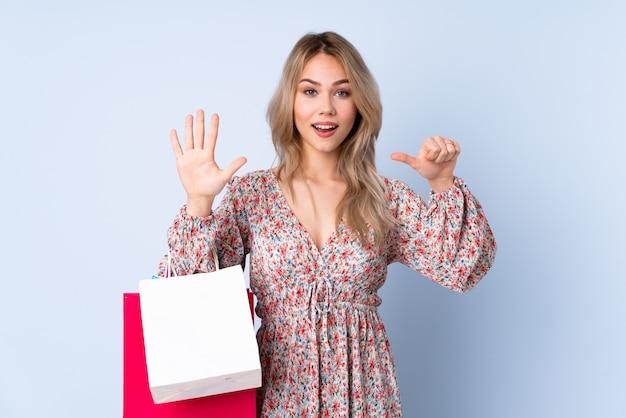Donna dell'adolescente con il sacchetto della spesa isolato sulla parete blu che conta sei con le dita