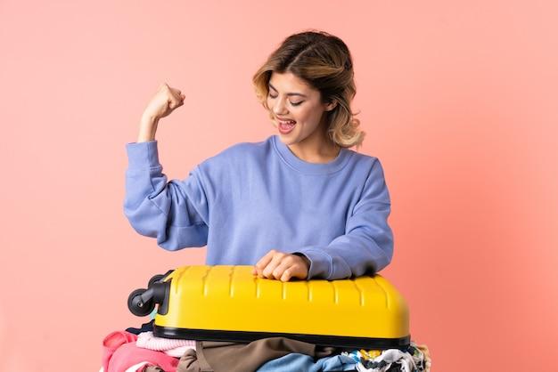 Donna dell'adolescente con insalata isolata sul colore rosa che celebra una vittoria