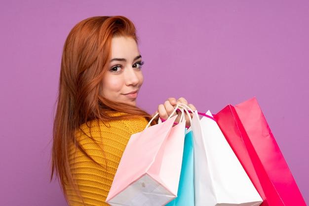 Donna dell'adolescente della testarossa sopra i sacchetti della spesa porpora isolati della tenuta della parete