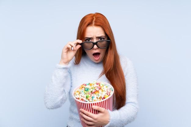 Donna dell'adolescente della testarossa sopra la parete blu isolata sorpresa con i vetri 3d e tenere un grande secchio di popcorn